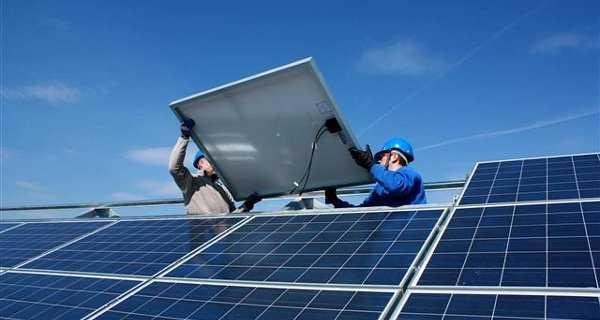 Operai al lavoro con pannelli fotovoltaici