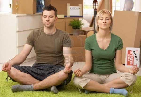 Giovane coppia che fa yoga in casa