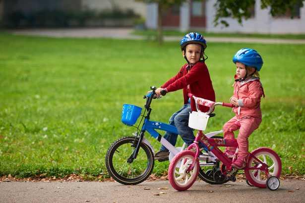 bambini che pedalano con biciclette tradizionali con e senza rotelle