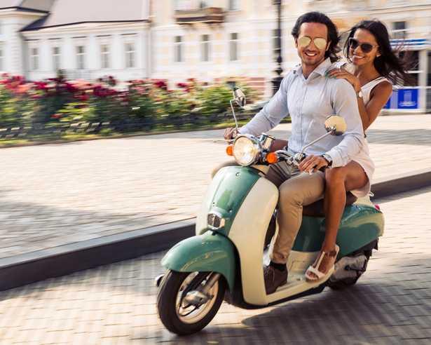 giovane coppia in sella ad una vespa scooter