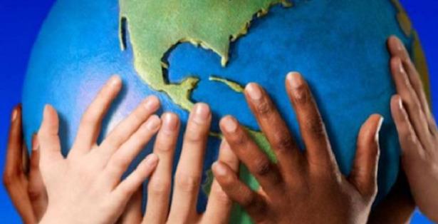 mani su mappamondo solidarietà